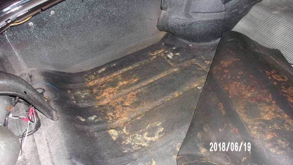 Pre-Buy Car Inspection - Photo of rust under mat in trunk